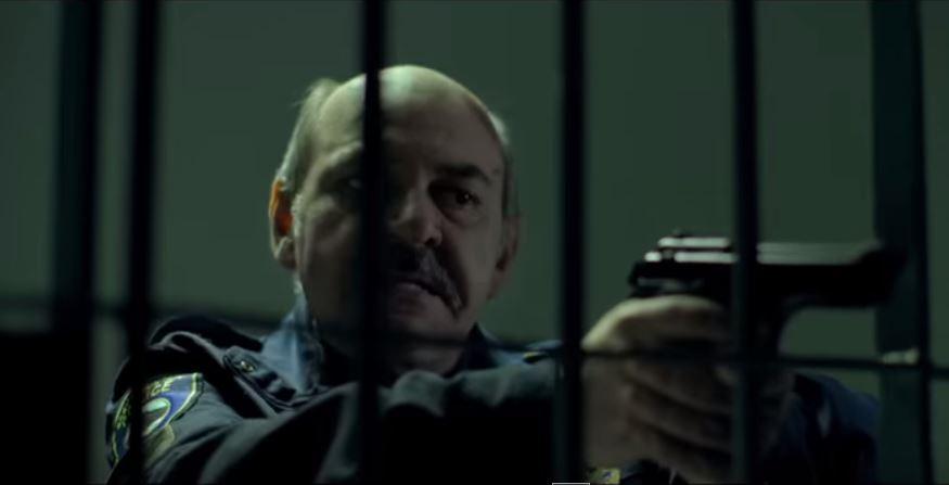 policjant mierzący z pistoletu do więźnia