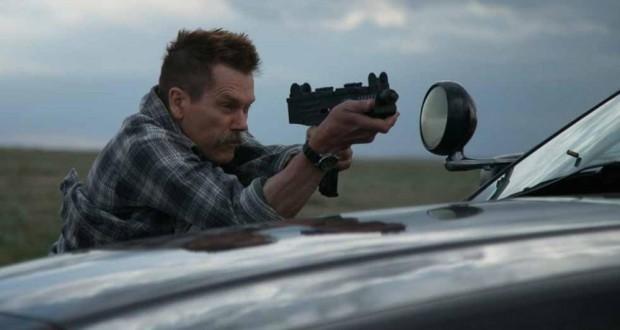recenzja filmu Cop Car, Kevin Bacon strzela z UZI.