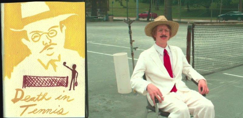 facet z wąsem i w kapeluszu siedzi na korcie tenisowym