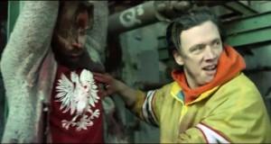 Trailery 2015. Napastnik torturuje mężczyznę w czerwonej koszulce z dużym białym Orłem