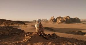 Matt Damon siedzi na wzniesieniu i obserwuje powierzchnię Marsa