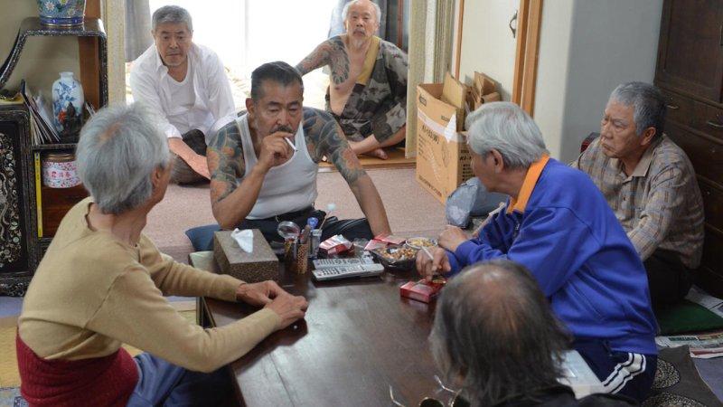 Ryuzo pali papierosa w towarzystwie swoich kolegów z yakuzy.