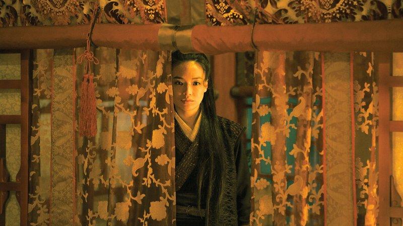 Qi Shu spogląda przez zasłony.