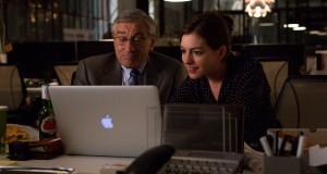 Robert De Niro i Anne Hathaway przed MacBookiem w filmie Praktykant